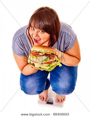 Woman weight loss on scales eating big hamburger. Isolated.