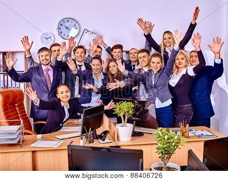Happy group business people with hand up together in office. Clock on wall.