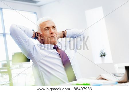 Businessman in office relaxing leaning back on chair