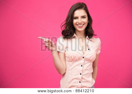 Happy young woman pointing finger away over pink background and looking at camera
