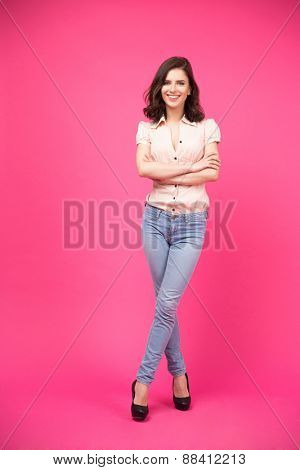 Full length portrait of a happy woman with arms folded standing over pink background. Looking at camera. Wearing in jeans and shirt