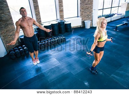 Fitness man and woman workout with jumping rope in crossfit gym