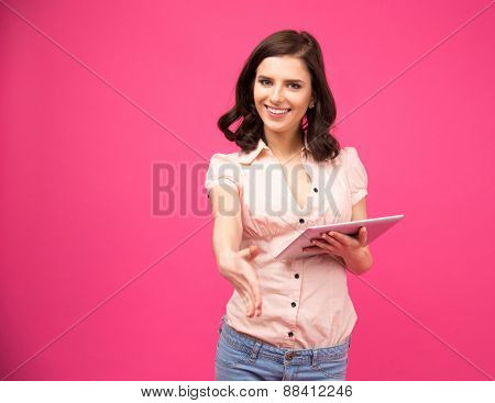 Smiling young woman holding tablet computer and stretching hand for handshake over pink background