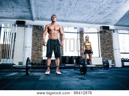 Fit man and woman workout with barbell at gym