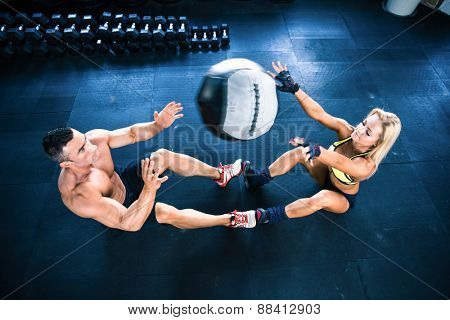 Muscular man and woman workout with fitball at gym