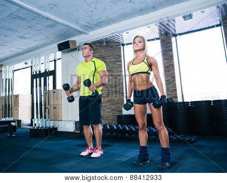 Woman and man working out with dumbbells at gym