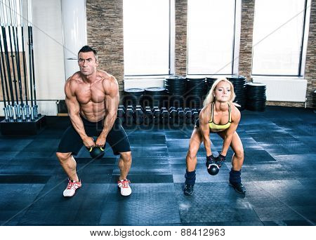 Muscular man and fit woman doing exercises with kettle ball at gym