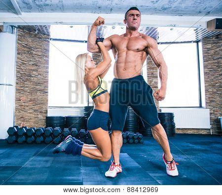 Sporty woman hanging on a hand of muscular man at gym
