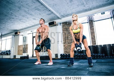 Muscular man and fit woman lifting kettle ball at gym