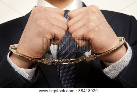 Arrested business man handcuffed hands. Close-up.