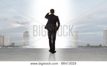 Businessman standing on a on road and looking at city