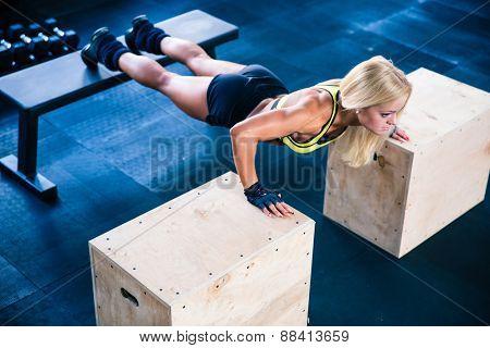 Beautiful sports woman doing push ups on fit box at gym