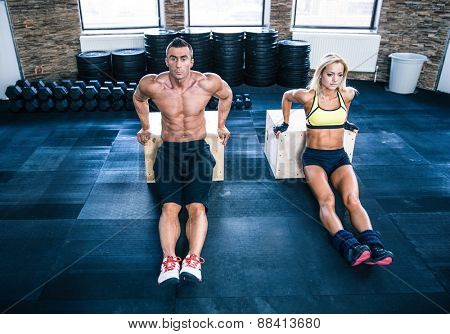 Man and woman workout with hands on fit box at gym