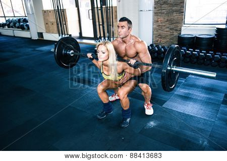 Woman workout with barbell with coach at gym