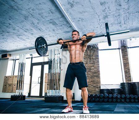 Muscular man lifting barbell at gym
