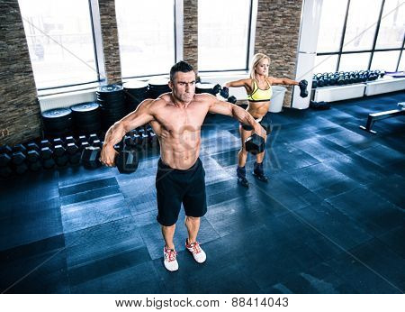 Muscular man and fit woman workout with dumbbells at gym