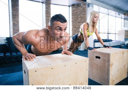 Woman and man doing push ups on fit box at gym