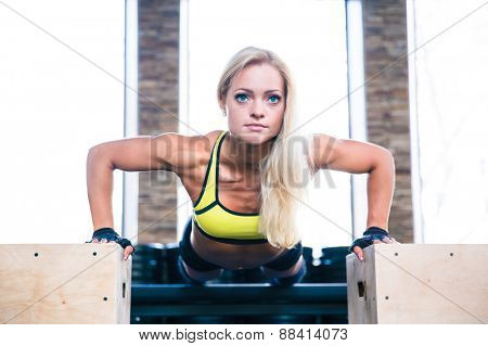 Young beautiful sports woman doing push ups on fit box at gym