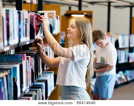 teenage girl in library choosing books