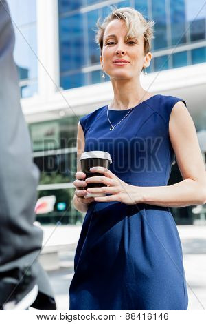Businesswoman standing next to her office and holding a coffee