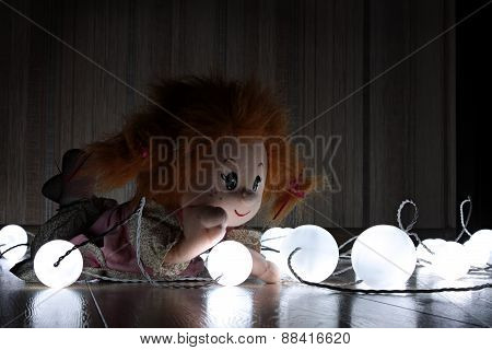 Doll lying on the floor among lanterns.