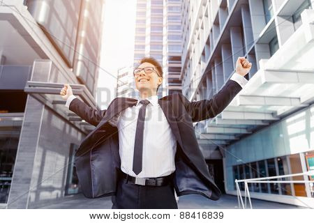 Businessman standing in street with his arms open