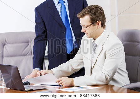 Young businessman in office showing documents to his boss
