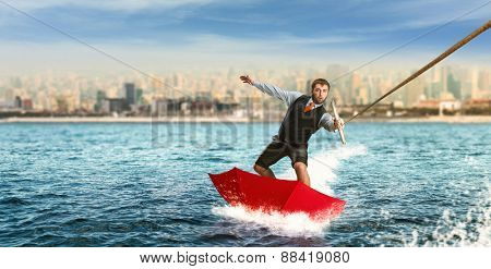 Businessman on water skis in umbrella