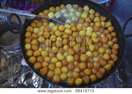 An Arabic sweet called Luqaimat is being fried in hot oil.