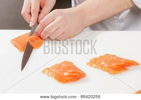 Sushi chef slices salmon
