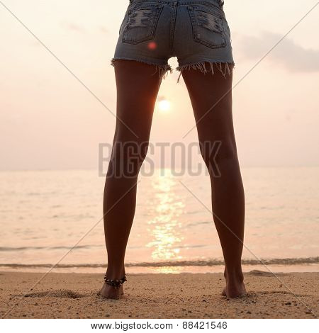 Young Woman  In Jeans Shorts Standing On Beach