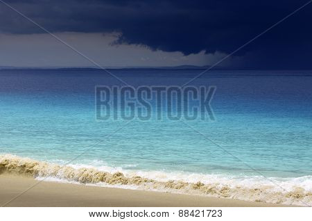 Tropical ocean white sand beach with storm clouds on the horizon