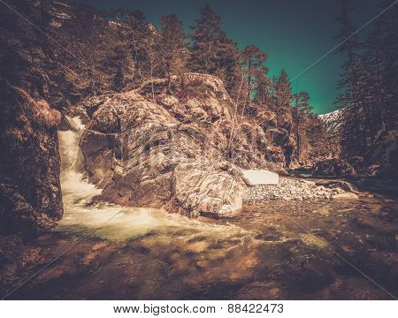 Fast river in mountain forest with little waterfall