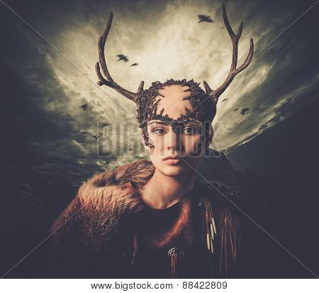 Woman shaman in ritual garment over dramatic stormy sky
