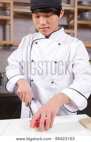 Cook cuts sushi rolls