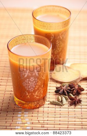 Masala chai tea in yellow glasses and spices on a straw mat