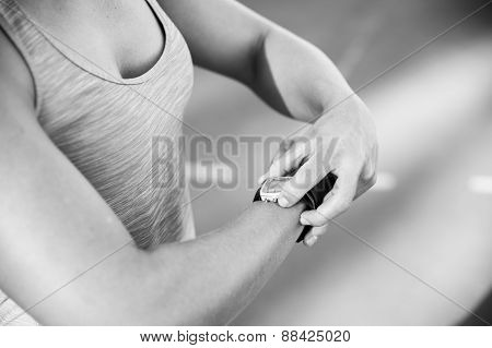 Close Up Black And White Image Of A Female Athlete Adjusting Her Heart Rate Monitor