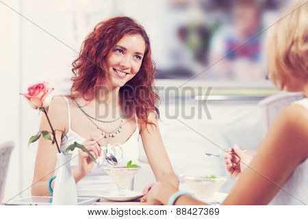Two pretty female friends meeting in cafe