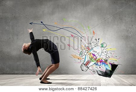 Young businesswoman evading colorful splashes flying from laptop