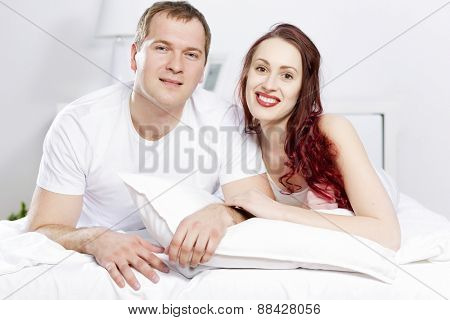Young couple talking while lying in bed in the morning