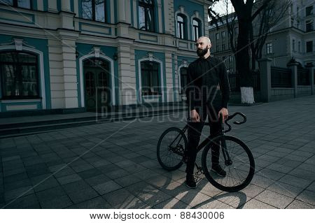 guy in black clothes stands with bike