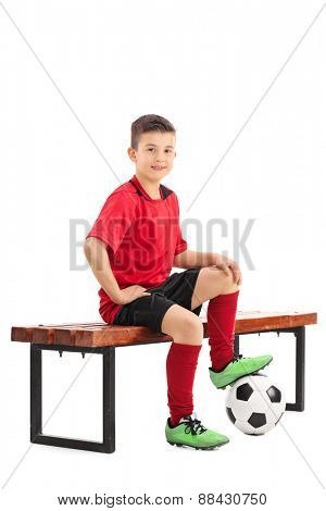 Junior football player in a red jersey sitting on a bench with a ball under his foot isolated on white background