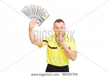 Furious football referee blowing a whistle, holding a stack of money and looking at the camera isolated on white background