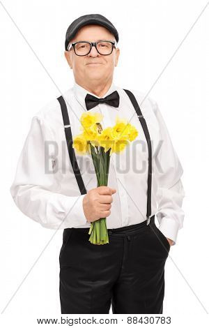 Fashionable senior gentleman holding a bunch of yellow tulips, smiling and looking at the camera isolated on white background
