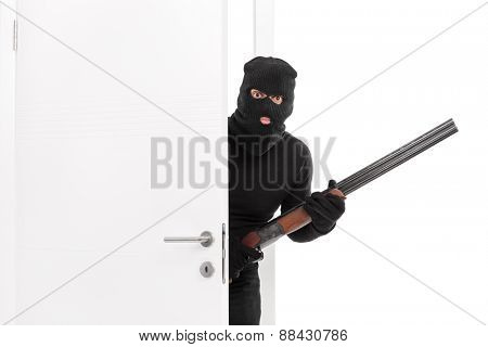 Masked terrorist entering a room and holding a shotgun rifle isolated on white background