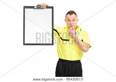 Angry football referee in a yellow shirt blowing a whistle and showing a blank paper on a clipboard isolated on white background