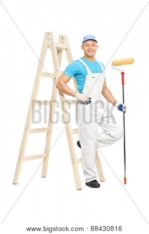 Full length portrait of a male house painter in a clean white overalls holding a paint roller and leaning on a ladder isolated on white background