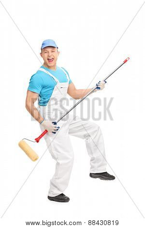 Full length portrait of a delighted male house painter playing guitar on a paint roller isolated on white background