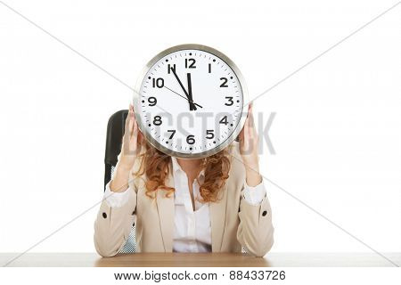 Businesswoman hiding behind clock by a desk.