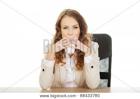 Business woman drinking coffee by a desk.